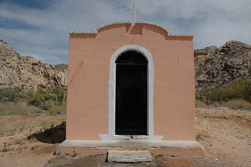 Small pink roadside shrine or chapel, white cross, similarly colored hills and pink rock, Sonora Desert, northern Mexico, along the border, Highway 2 by Wonderlane