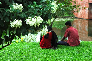 lovers in paradise, two people sit side by side on a lush grass near a brick bridge over a lily pond, inside a beautiful garden at জাতীয় স্মৃতি সৌধ Jatiyo Smriti Soudho Independence memorial park, Savar, Dhania, Dhaka, Bangladesh