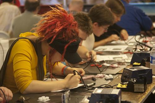 Un atelier de soudure dans une Maker Faire. Au premier plan, une jeune femme aux cheveux rouges et coiffée d'une casquette et plusieurs autres visiteurs en arrière-plan suivent des instructions de montage, fer à souder à la main, sur une longue table.