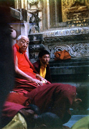 His Holiness Dilgo Khyentse Rinpoche at the Mahabodhi Stupa, watching people prostrate, near the Bodhi Tree, sculptural decoration and gold on a statue, Bodhgaya, India, 1990, photo by Gary by Wonderlane