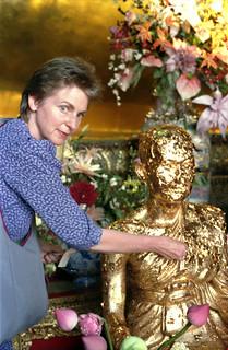Sangha member Virginia Johnson applying gold leaf offering to Buddhist master statue, flowers, shrine, Bangkok, Thailand, pilgrimage, 1993