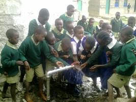 Elever leger med vand fra den renoverede brønd ved Githabai Primary School