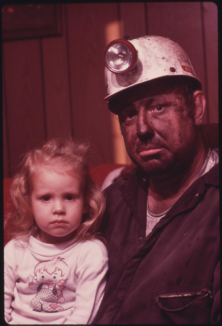 DOCUMERICA: Miner Wayne Gipson, 39, with His Daughter Tabitha, 3. He Has Just Gotten Home From His Job as a Conveyor Belt Operator in a Non-Union Mine. as Soon as He Arrives He Takes a Shower and Changes Into Clothes to Do Livestock Chores with His Two Sons. Gipson Was Born and Raised in Palmer, Tennessee, But Now Lives with His Family near Gruetli, near Chattanooga. He Moved North to Work and Married There, But Returned Because He and His Wife Think It Is a Better Place to Live. December, 1974 by Jack Corn.