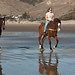 Two women at the reins - female equestrians horse riders on the wet sand