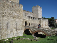 The entrance to the castle. In medieval times there must have been a draw bridge here, instead of the permanent stone bridge, and deeper moats filled with water.  The Castelo de São Jorge was originally built by Moslems in the 11th century, when Lisbon was still ruled by them. It was designed to withstand long sieges with many creative defensive features, such as Traitor's gates and false doors as well as thick and tall walls and turrets.