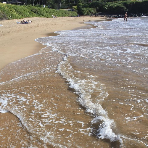 Clear water rushes over golden sands on a beach in Wailea.