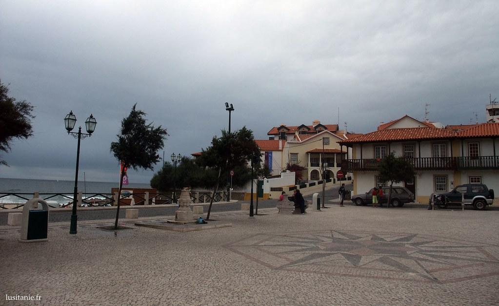 La place en bord de mer, avec les trottoirs pavés à la portugaise. Au sol, une grande rose des vents décorative.