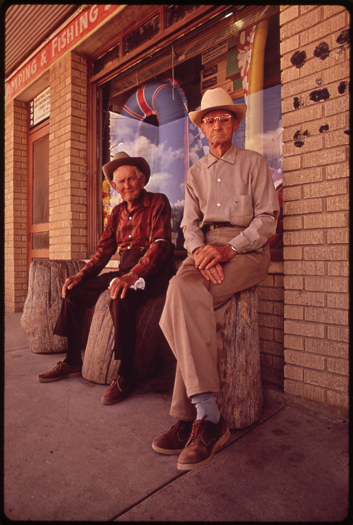 "W.G. Leistikon, 70; and John Ricks, 87, in Front of the Local Drugstore. Stumps in Front of Store Are Reserved for the ""Old-Timers"" 11/1972"