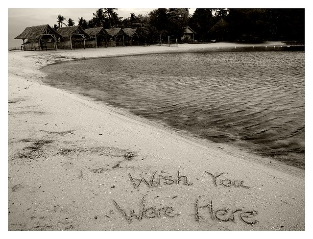 Wish You Were Here message written on the sand