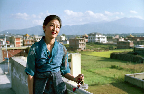 Tibetan woman, with a wistful expression - behind her is Tibet, wearing a blue chuba and a mala, holding car and house keys, on the roof of a house, overlooking the fields, Boudha, Nepal in 1990 by Wonderlane