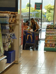 Woman with Child at Check Out Counter with Blue Shopping Cart.