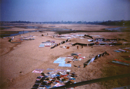 Close up wallas washing clothes, saris, sheets and bedding in a river and hanging them to dry, from a Buddhist pilgrimage tour bus, on a bridge, town, Northern India, 1993 by Wonderlane
