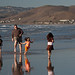 Three Children with their Father romp in the chilly water in Morro Bay