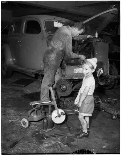 Young boy with dinky in car workshop while his father (?) services a car, Bondi, 6 October 1955 / Ern McQuillan by State Library of New South Wales collection