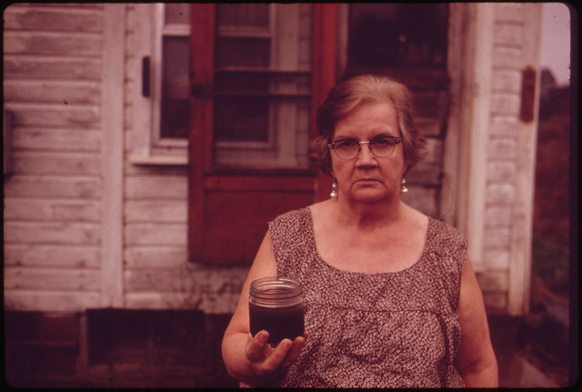 Mary Workman Holds A Jar of Undrinkable Water That Comes from Her Well, and Has Filed A Damage Suit Against the Hanna Coal Company ..., 10/1973