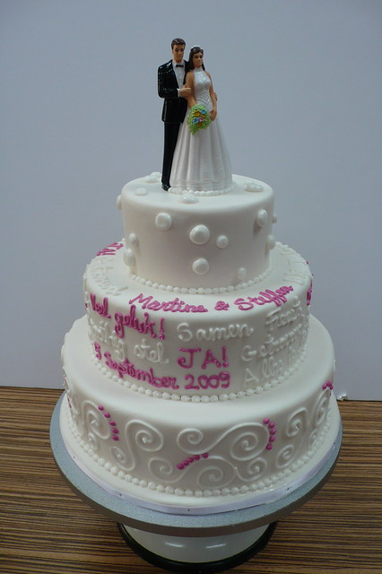 Iced wedding cake with writing and swirls with topper