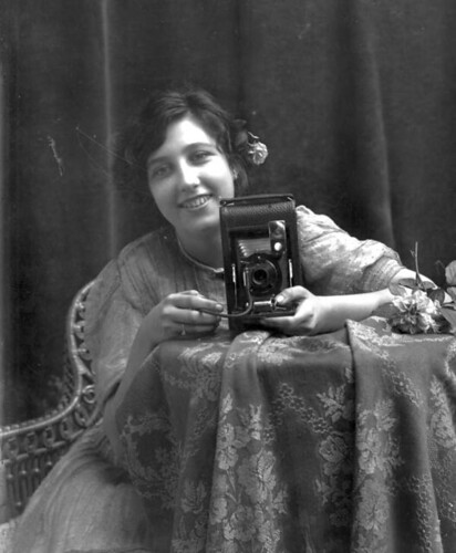 Young smiling woman, holding a camera