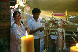 American Tibetan Buddhist sangha member, Diane, purchasing gold leaf to apply to statues of the Buddhas and Bodhisattvas as offerings, candles, statues covered with gold leaf, Bangkok temple, Thailand, Pilgrimage, 1993