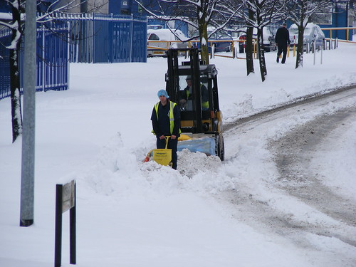 Forklift truck moving snow