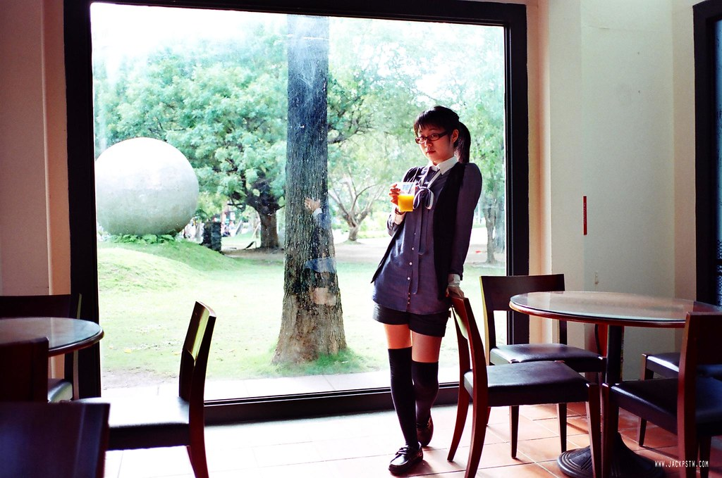 A girl holds a glass beside the window that look like a painting