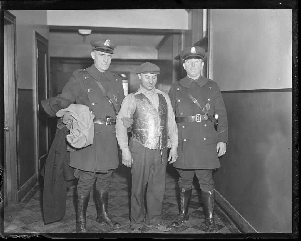 Francesco Santorelli, wearing bullet proof vest, accompanied by patrolmen Alfred Pearson and Patrick Conroy (R).