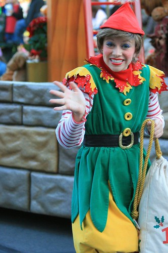 Woman dressed as elf, waving.