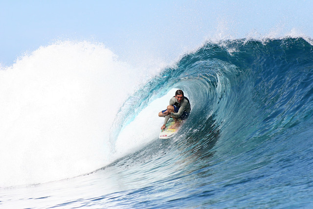 A surfer surfing a decent wave at Teahupoo, Tahiti.