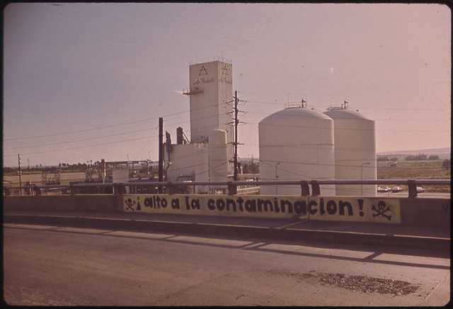 DOCUMERICA: Sign on Bridge near Ppg Plant Protests Air Pollution Ponce, Puerto Rico 02/1973 by John Vachon.