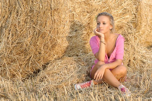 pink light sunset shadow summer portrait woman sunlight white flower cute sexy girl beautiful beauty smile yellow horizontal closeup female rural evening countryside md warm pretty european sitting looking legs gorgeous country young straw calm sneakers trainers blond shade thinking thatch hay pastoral tender chisinau tanned crossed caucasian plimsolls gymshoes haulm republicofmoldova