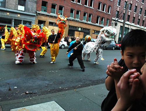 Two boys chat and keep their hands warm watching the New Years Dragon and Lions Dance, Seattle, Washington, USA by Wonderlane