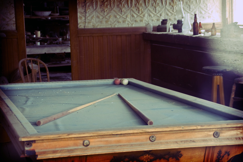 A battered, dusty pool table