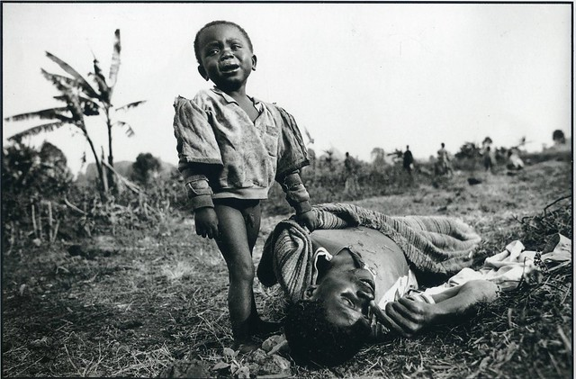 Rwandan toddler cries and clings to his dead father, who died moments before of cholera. The two had fled the Hutu-Tutsi violence in Rwanda and come to Zaire for safety, by David Turnley 1994