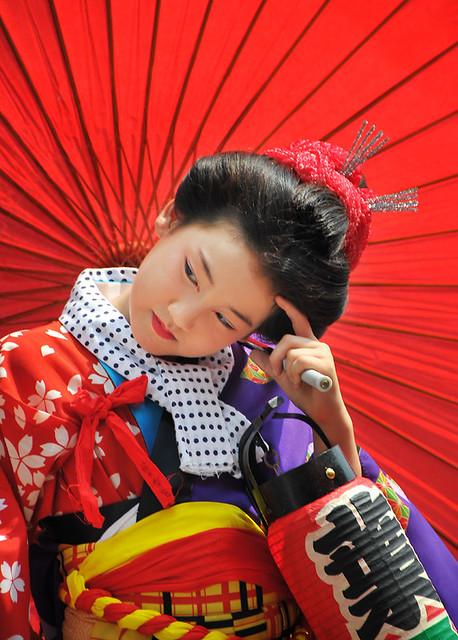resting under her red umbrella