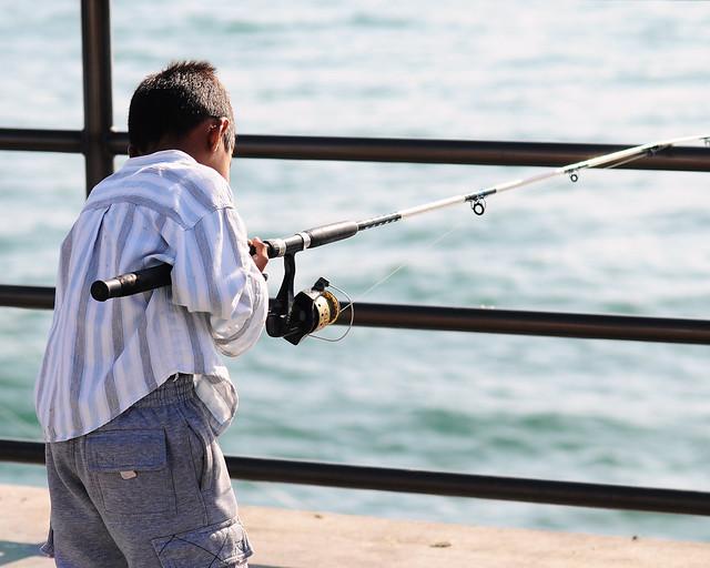 Young boy reeling in a fish at huntington beach pier for Huntington beach pier fishing