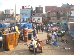 city(0.0), slum(0.0), town(1.0), market(1.0), bazaar(1.0), flea market(1.0), marketplace(1.0), public space(1.0), neighbourhood(1.0),