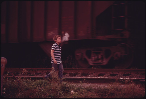 The Cool Morning Air Condenses a Boy's Breath as He Walks Along a Coal Car on His Way to School in Cumberland, Kentucky, in Harlan County 10/1974
