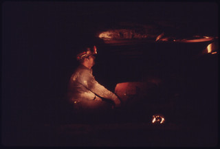 Miner Bathed in the Glow of a Co-Worker's Lamp Is Shown with a Shutter Car Used for Transporting Safety Men Or Other Small Groups 04/1974
