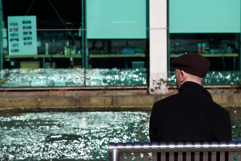 Hombre cerca el banco con reflexiones