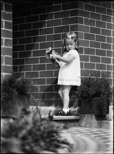 Girl (Cook family) on front doorstep carrying a toy 'Life Savers' truck