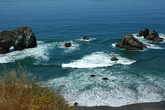 Rock arch, islets, double fan waves breaking in the beautiful turquoise Pacific Ocean, north of Fort Bragg, California, USA
