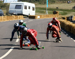 inline speed skating(0.0), sports(1.0), race(1.0), recreation(1.0), outdoor recreation(1.0), longboarding(1.0), extreme sport(1.0), longboard(1.0), race track(1.0),