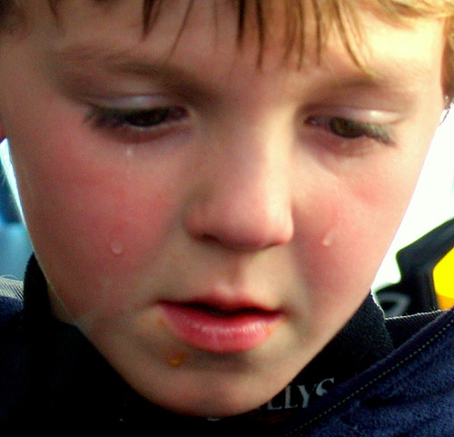 A boy crying because he is sad his hot dog fell