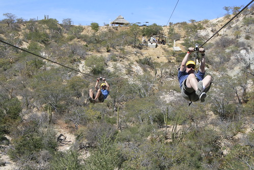 Two people zip lining through the desert