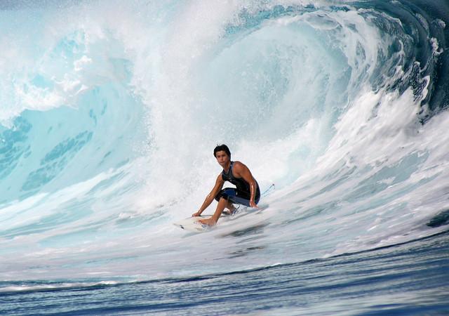 A surfer surfing a big wave at Teahupoo, Tahiti.
