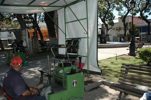 In use, a old green metal shoe shine chair, awning, public park, Guadalajara, Jalisco, Mexico by Wonderlane