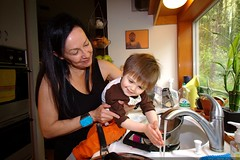 grandma helps a grandson wash his hands in the kitch…
