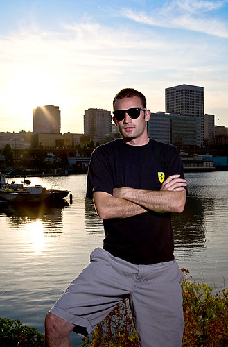 Douche McLaren fan in a Ferreri shirt with knock off Rayban sunglasses perched on cord wood next to where they make tug boats as the sun sinks below a megar skyline beside a former federal superfund s
