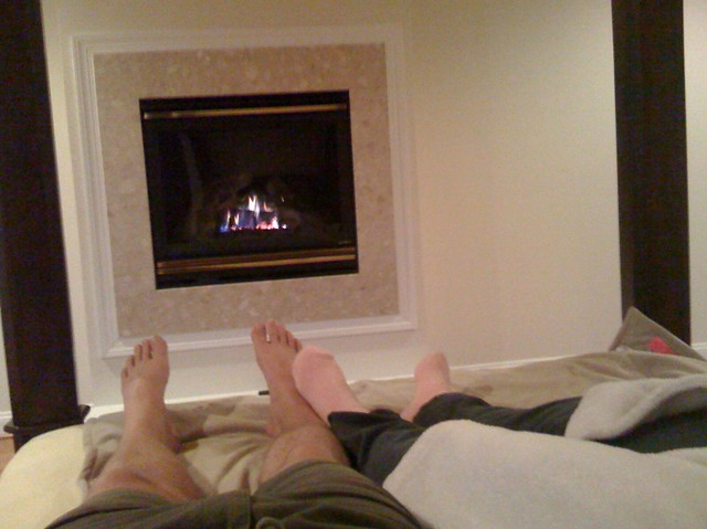 Two really tired people relax by a fire in the bed at thei ...