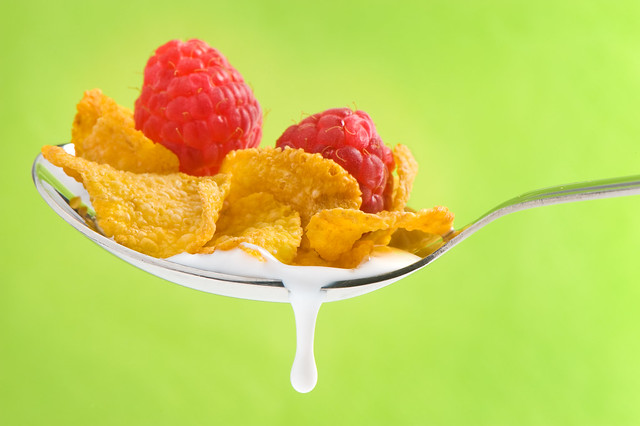 spoon with corn flakes and raspberry on green background