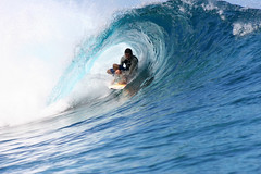 Surfing in the tube at Teahupoo, Tahiti.